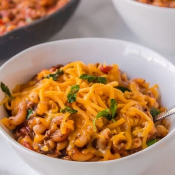 old fashioned goulash with cheddar cheese on top served in a white bowl