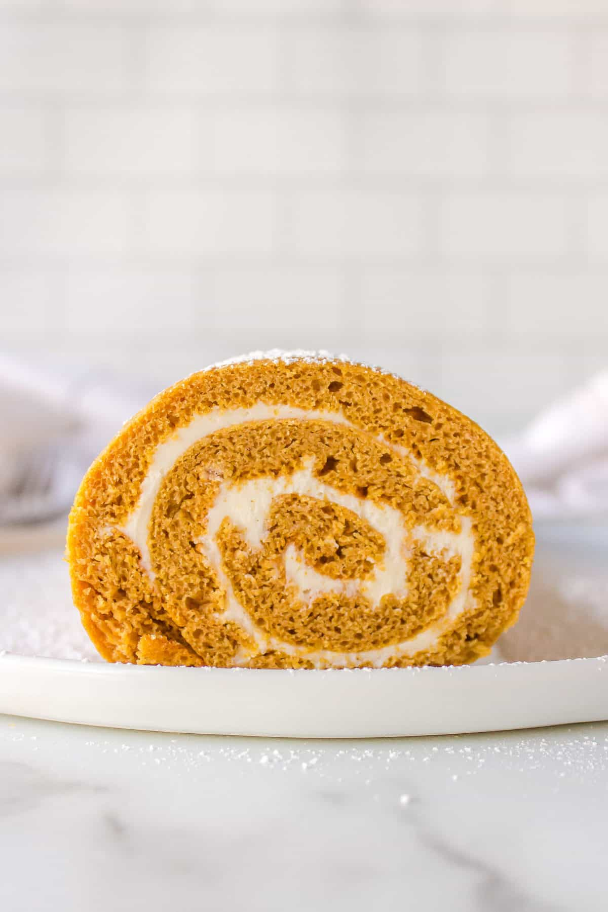 sliced cross section of cake mix pumpkin roll with cream cheese frosting served on a white plate
