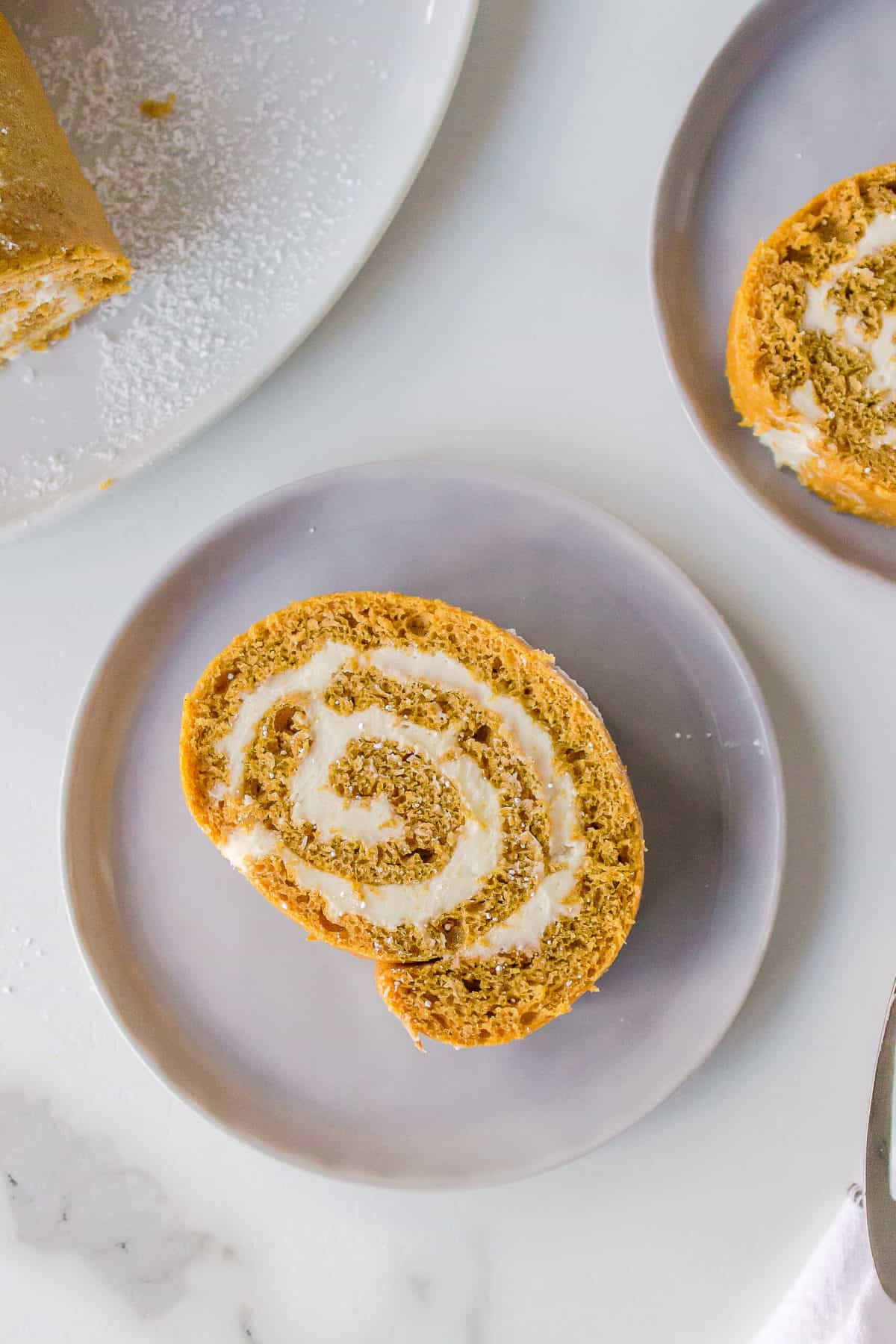 slice of a cake mix pumpkin roll with cream cheese frosting served on a taupe plate