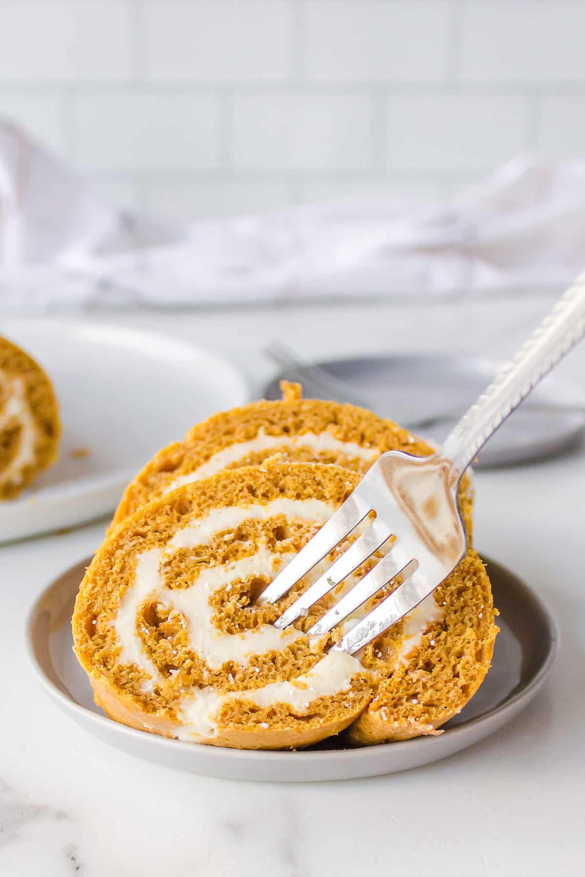 fork in cake mix pumpkin roll with cream cheese frosting served on a taupe plate