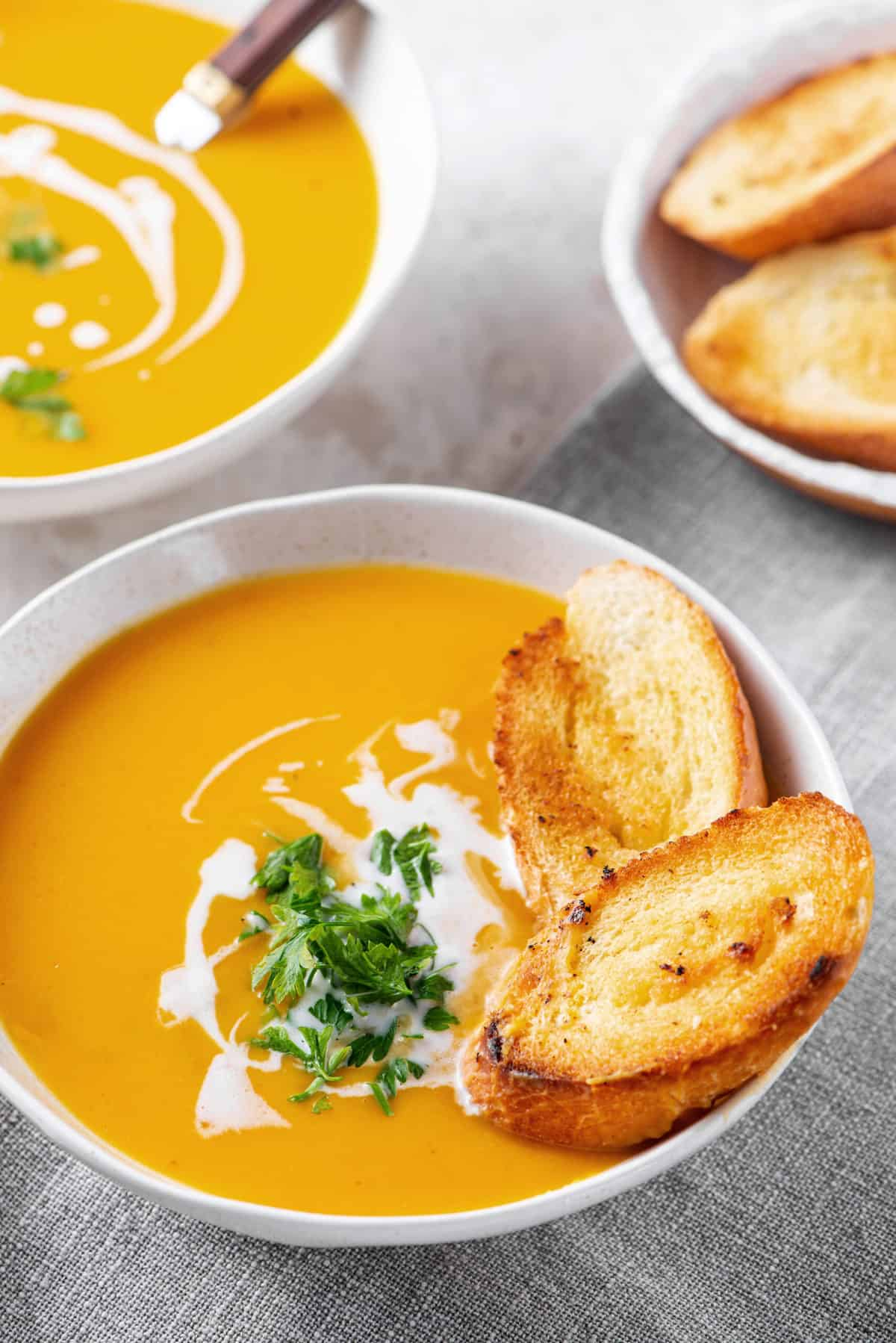 butternut squash soup with white toasted bread in a white bowl
