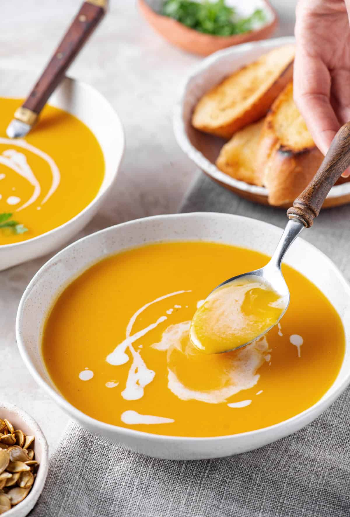 butternut squash soup with spoon served in a white bowl