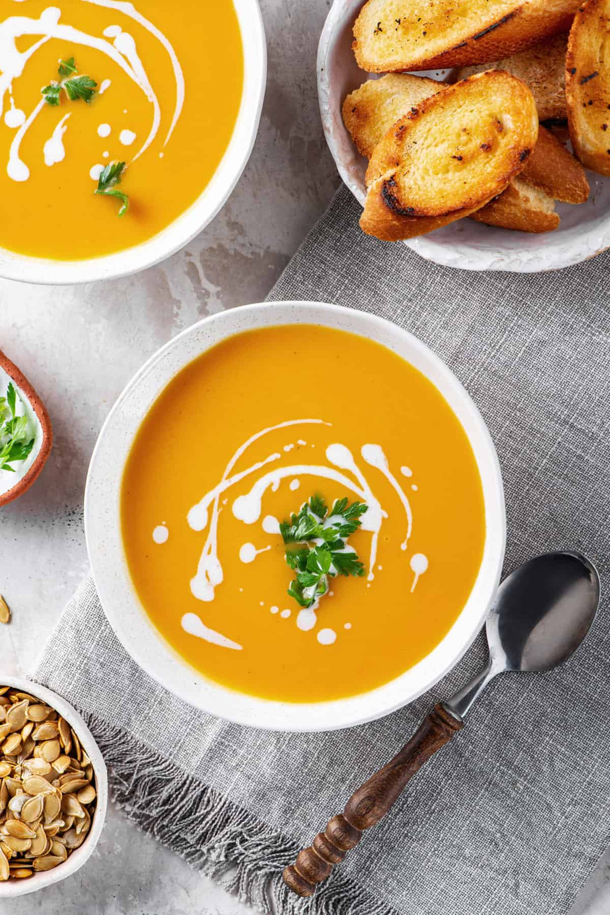 butternut squash soup with a sour cream swirl design and cilantro served in a white bowl and a silver spoon sitting next to the bowl